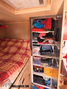 The wardrobe is beside the bed.
