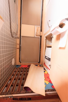 Shower tray exposed. There is a regular shower tray under the timber grid. The toilet is in the press on the right.