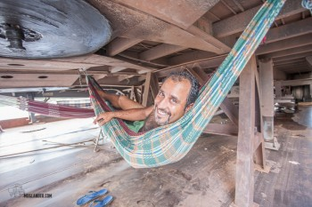 Brazilian truck driver relaxing out of the sun under a trailer.